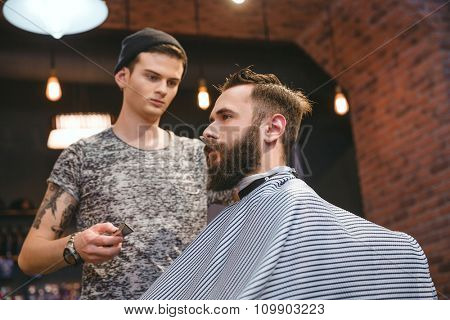 Concentrated skillful hairdresser making haircut to young bearded handsome man at barbershop