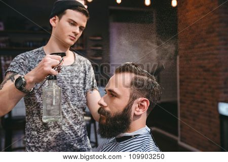 Handsome concentrated hairstylist sprinkles with water hair of attractive client with beard at barber shop