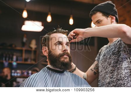 Handsome skillful barber cutting hair of young attractive man with beard at barbershop