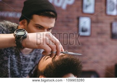 Closeup of young concentrated barber grooming beard of handsome man with scissors at barber shop