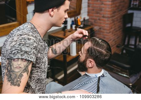 Young hairstylist with tattoo combing hair of male client with a comb in hair salon