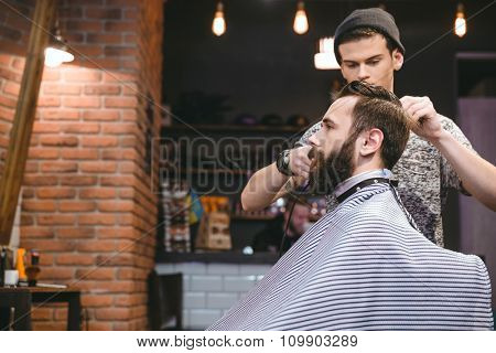 Young handsome hairstylist making men's haircut to a attractive bearded male in the beauty salon