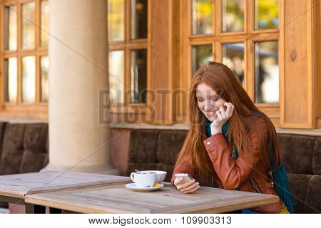 Cute smiling happy young female with beautiful long red hair in leather jacket drinking coffee and using smartphone in outdoor cafe