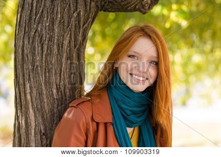 Young positive smiling redhead woman in leather jacket and scarf posing near the tree in park