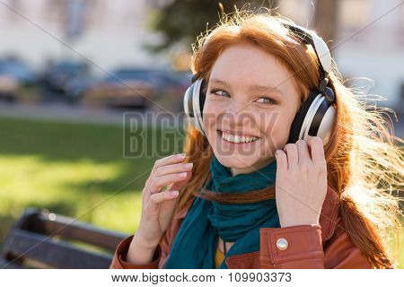 Portrait of happy smiling redhead young lady in bright scarf enjoying music on the bench in the park