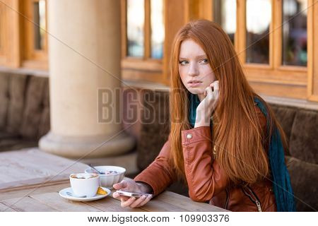 Beautiful redhead young woman with long hair in leather jacket using cellphone and waiting for somebody in outdoor cafe