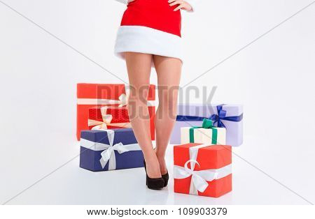 Closeup portrait of sexy female legs in santa claus cloth with present boxes isolated on a white background