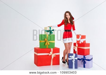 Full length portrait of a happy woman standing with many present boxes isolated on a white background