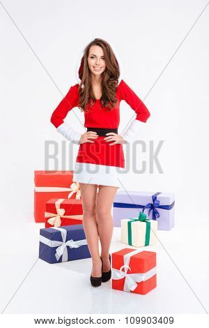 Full length portrait of a smiling woman standing with many present boxes isolated on a white background