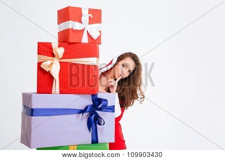 Attractive curly young woman in red santa claus costume with hood hiding behind present boxes isolated over white background