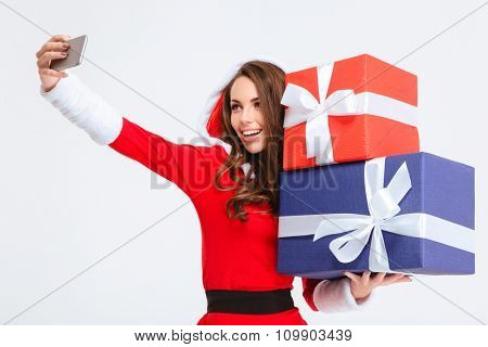 Joyful pretty young woman in red santa claus costume with hood holding present boxes and making selfie using her cellphone over white background