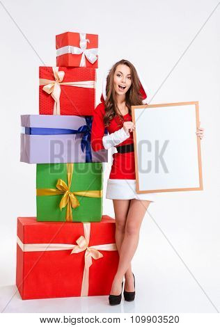 Full length portrait of a cheerful woman in santa claus cloth holding blank board isolated on a white background