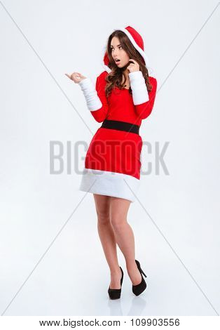 Shocked beautiful curly young woman in red santa claus costume with hood pointing away and looking away over white background