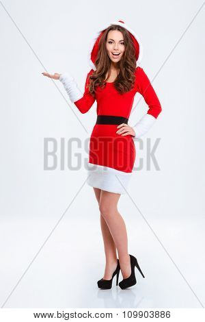 Full length portrait of happy beautiful curly young woman in red santa claus costume with hood holding copyspace on the palm isolated on white background