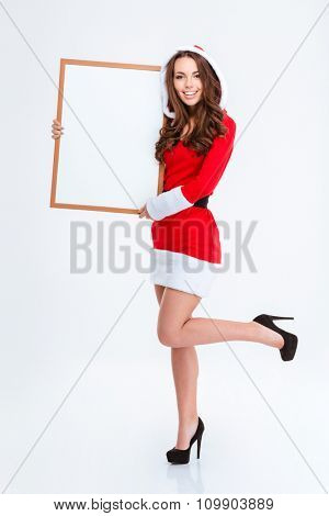 Beautiful smiling curly young girl in red santa claus costume with hood and shoes with high heels holding blank board over white background