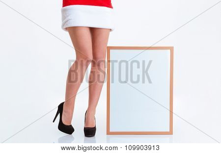 Closeup portrait of a sexy female legs in santa claus cloth and blank board isolated on a white background