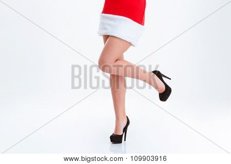 Closeup portrait of a sexy female legs in santa claus cloth isolated on a white bakground