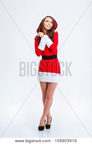 Full length portrait of inspired dreaming curly girl in red santa claus dress with hood on white background