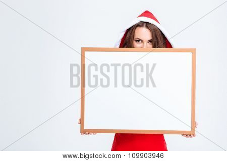 Attractive joyful girl in costume of santa claus with hood hiding behind the blank board over white background