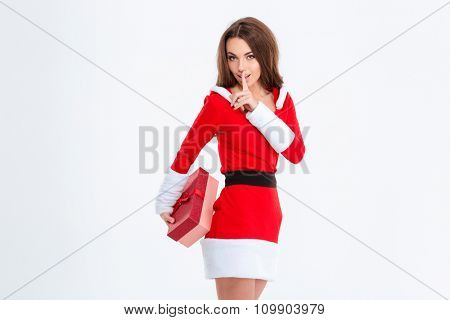 Portrait of a beautiful woman in santa claus cloth holding gift box and showing finger over lips isolated on a white background