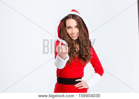 Portrait of a happy woman in santa cloths showing come to me gesture isolated on a white background