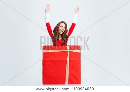 Joyful beautiful curly excited girl in red santa claus costume with hood jumping out of present box over white background