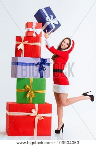 Joyful positive pretty young woman in red santa claus dress with hood making pyramid with colorful gifts over white background