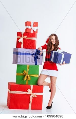 Full length portrait of lovely positive girl in red santa claus dress with hood posing with colorful presents over white background