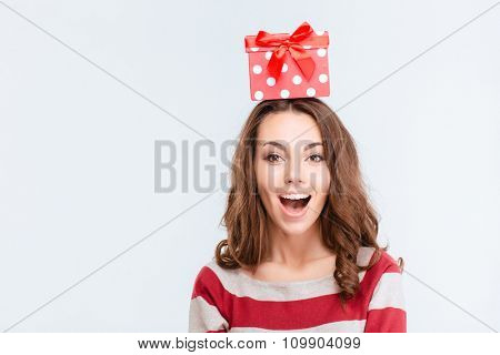 Portrait of a cheerful woman with gift box on head standing isolated on a white background