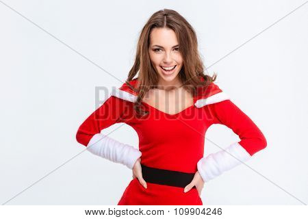 Beautiful happy excited young woman in red santa claus costume standing with hands on waist on white background