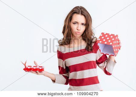 Portrait of a sad woman holding empty gift box isolated on a white background