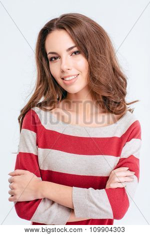 Portrait of a smiling charming woman standing with arms folded isolated on a white background and looking at camera