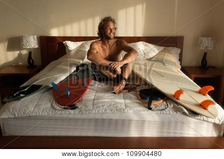 Surfer wake-up with his boards in bed