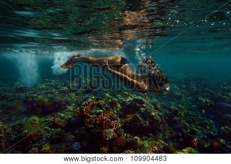 Underwater shoot of a relaxed smiling woman flying in a swimming pool in lotus position