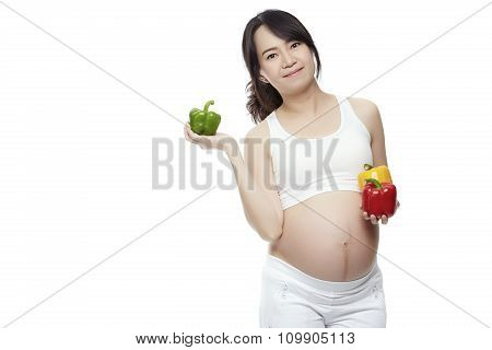 The Young Pregnant Woman Holding Peppers On A White Background.