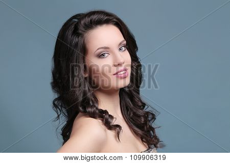 Beautiful woman with curly hair on a blue background