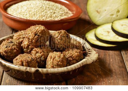 some vegan meatballs in an earthenware plate on a rustic wooden table, with some vegetables in the background