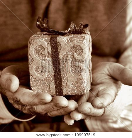 closeup of an old caucasian man with a gift in his hands, in sepia toning