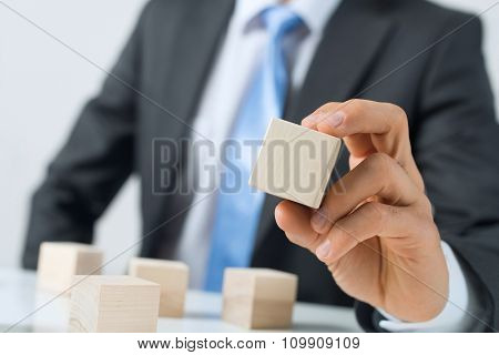 Businessman making tower with blocks