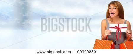 Shopping woman with envelope and gifts over blue background.