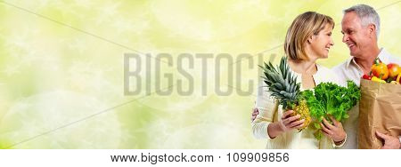Senior couple with vegetables over green background. Healthy diet.