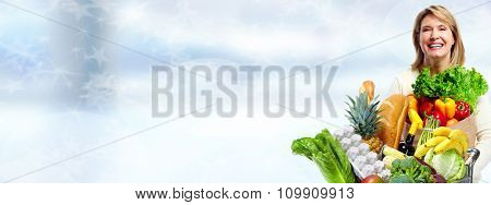 Senior woman with vegetables over blue background. Healthy diet.