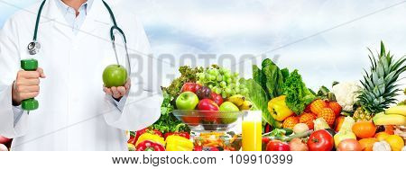 Doctor woman hands with apple and dumbbell over food background.