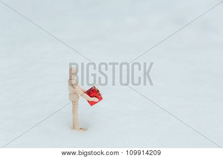 Wooden Mannequin With The Gift On The Snow