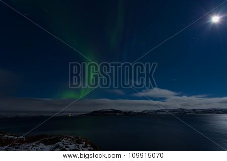 Aurora In The Sky In A Full Moon Night On The Shores Of The Barents Sea