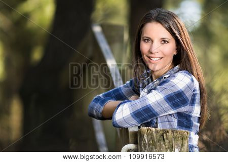 Beautiful smiling woman leaning on fence