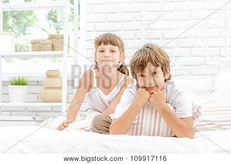 two little happy kids playing on white bed at home