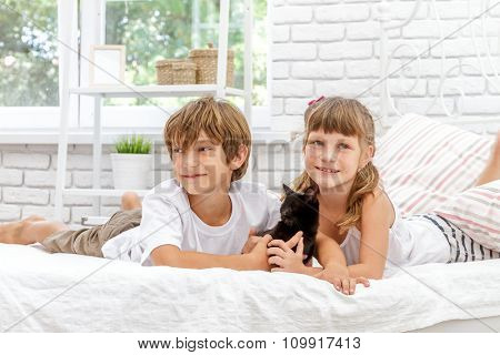 two little happy kids playing with black cat on white bed at home