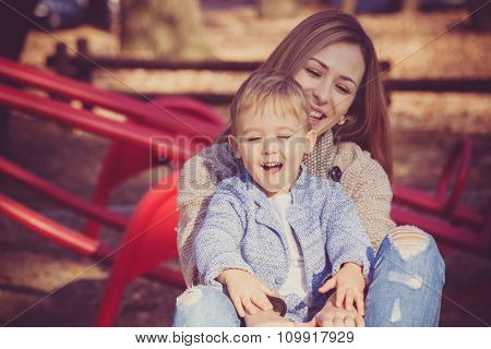 life is beautiful when you're a kid, child with his mother enjoy on roundabout in park, autumn day, selective focus