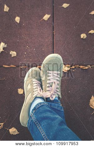 woman legs in sneakers, autumn leaves, shot from above, focus on shoes